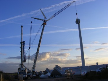 renewables first - Final fixing of the wind turbine generator as the sun goes down.